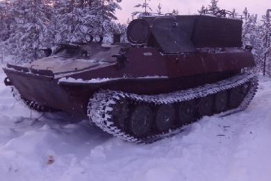 МТЛБ красного цвета на снегу, вид сбоку